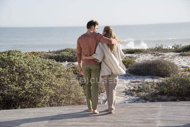 Счастливая пара, гуляющая по растительности на морском побережье — стоковое фото