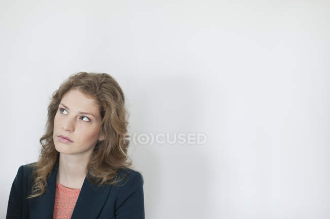 Portrait of thoughtful woman in jacket looking up against white wall — Stock Photo