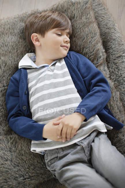 Descontraído menino com os olhos fechados deitado no travesseiro fofo — Fotografia de Stock