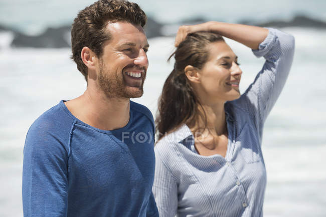Couple heureux regardant loin sur la plage — Photo de stock