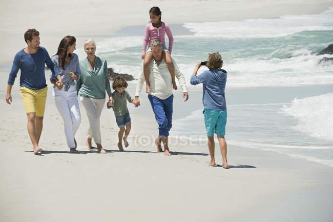 Мальчик фотографирует семью, гуляющую по песчаному пляжу — стоковое фото