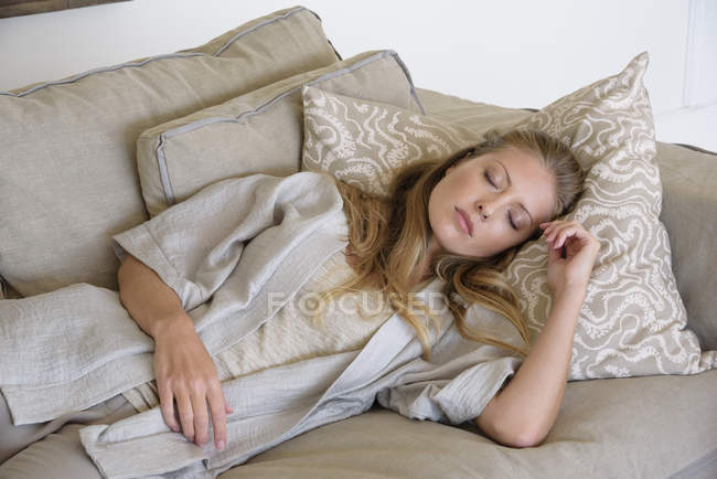 Woman with eyes closed relaxing on couch at home — Stock Photo