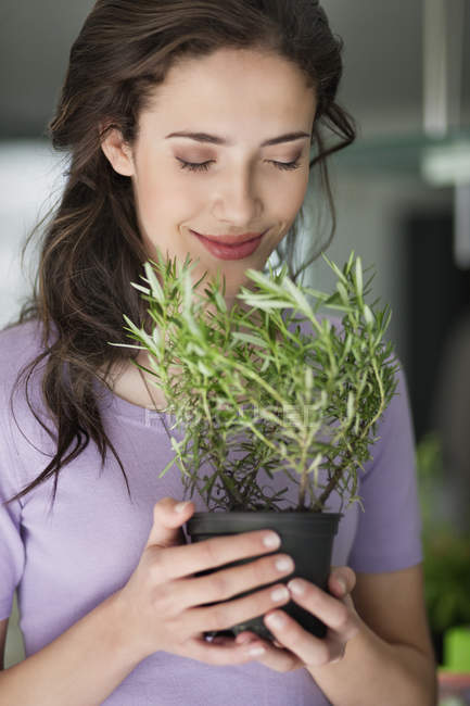 Smiling woman smelling potted rosemary plant — Stock Photo
