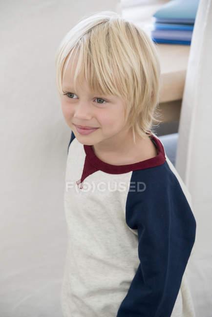 Gros plan d'un petit garçon heureux aux cheveux blonds regardant loin à l'intérieur — Photo de stock