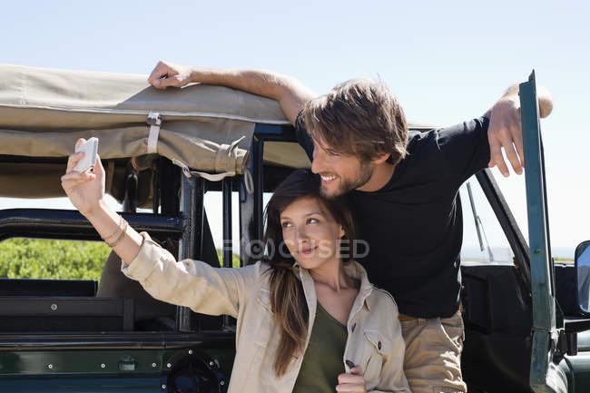 Femme avec petit ami prenant selfie avec téléphone portable devant fourgon ouvert — Photo de stock