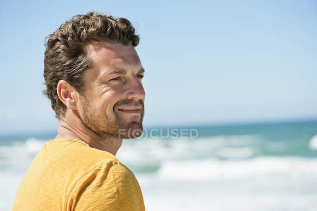 Thoughtful man smiling in front of waving sea — Stock Photo