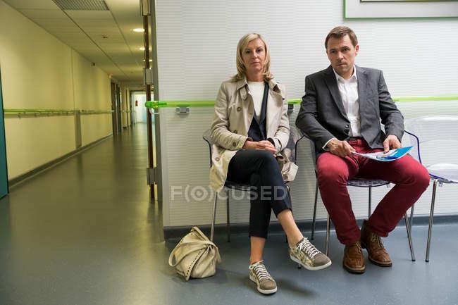 Пара сидящих в зоне ожидания больницы — стоковое фото