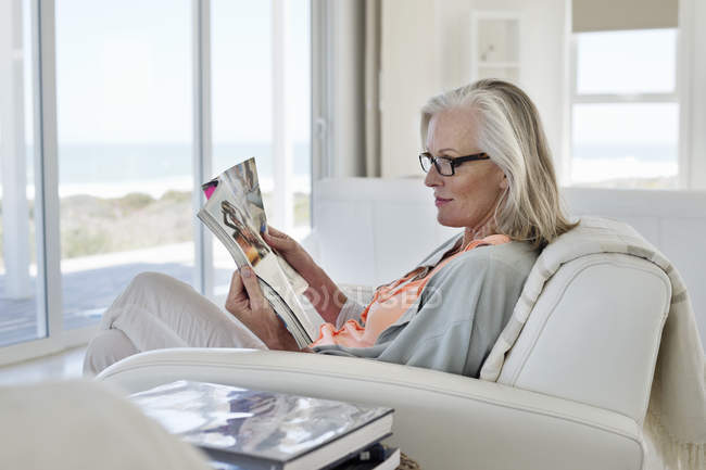 Woman Sitting On Couch And Reading Magazine At Home Elegancy