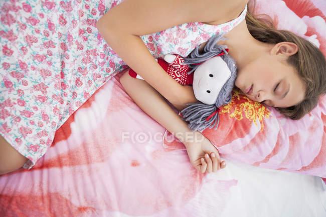 Innocent teenage girl sleeping on bed with rag doll — Stock Photo