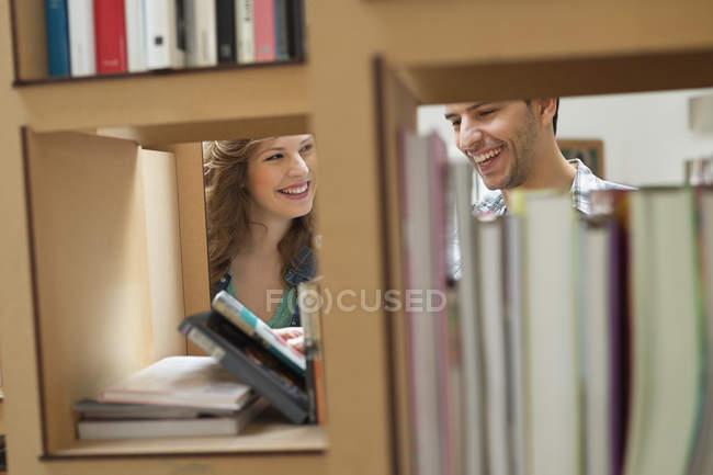 Couple choosing books from bookshelves in library — Stock Photo