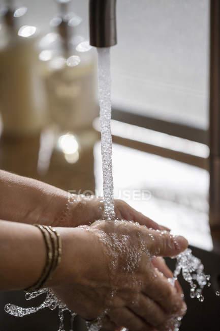 Lavarse las manos en el lavabo del baño - foto de stock
