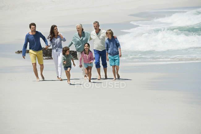 Счастливая семья гуляет по песчаному пляжу — стоковое фото