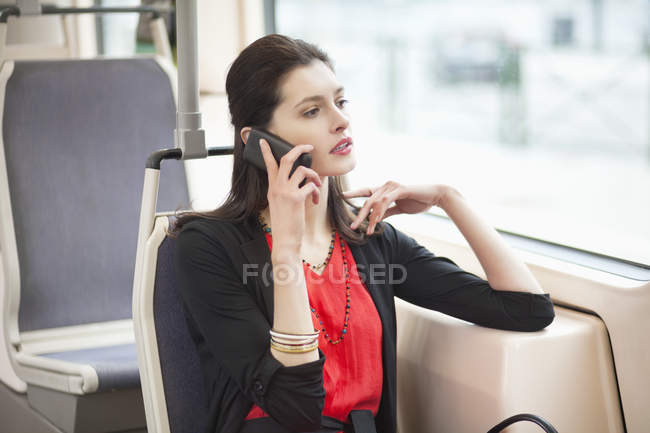 Woman traveling in bus and talking on mobile phone — Stock Photo