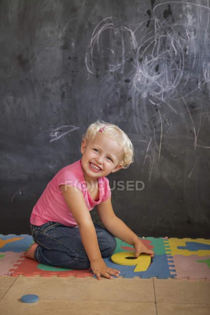 Sorrindo bonito menina brincando com quebra-cabeça número na frente de um quadro negro — Fotografia de Stock