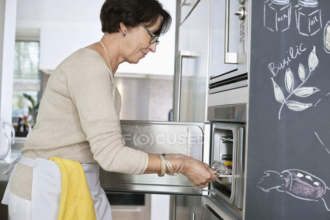 Senior woman putting tray of seafood into oven in kitchen — Stockfoto