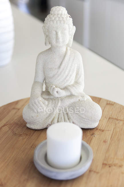 Close-up of Buddha statue with candle on table — Stock Photo
