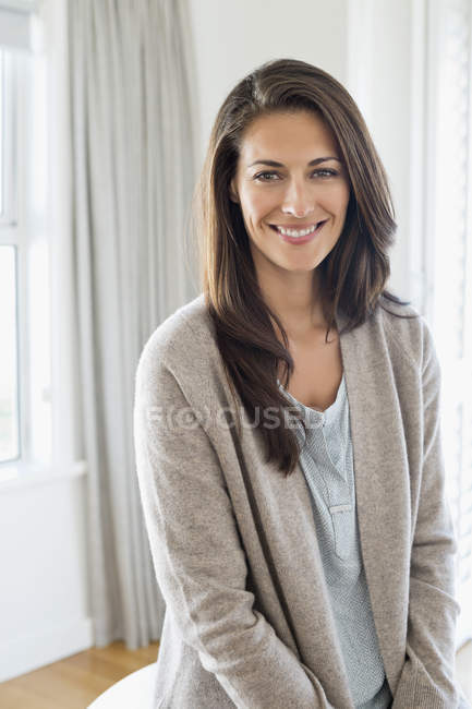 Portrait of smiling brunette woman standing at home — Stock Photo