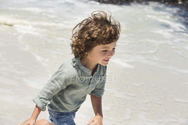 Smiling little boy running on sea beach — Stock Photo