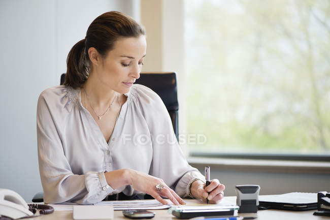 Elegant businesswoman working at desk in office — Stockfoto