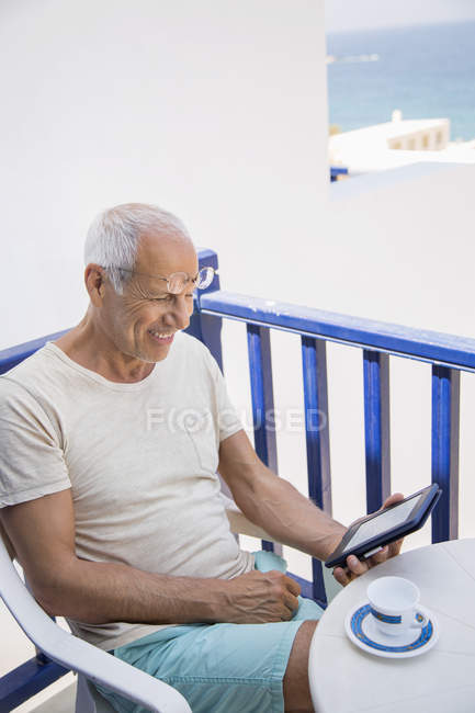 Happy senior man using a digital tablet on balcony — Stock Photo