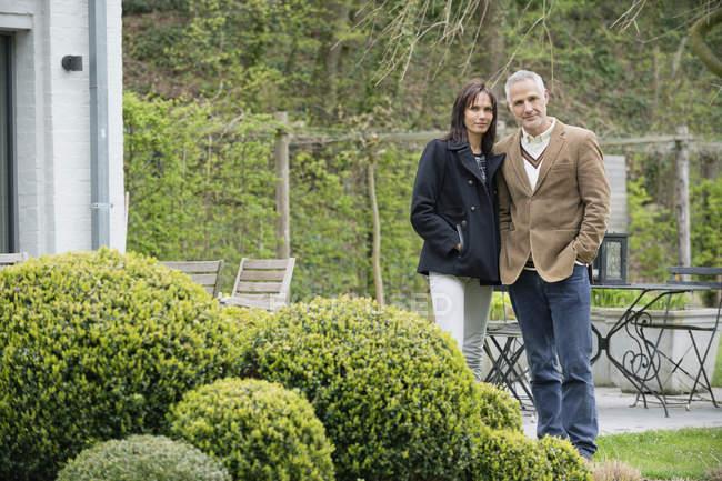 Portrait of mature couple standing in garden — Stock Photo