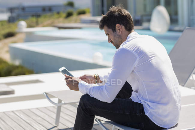 Man using smartphone deckchair on terrace — Stock Photo