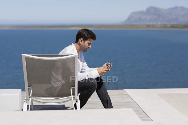 Handsome man sitting on deckchair at lake shore and using smartphone — Stock Photo