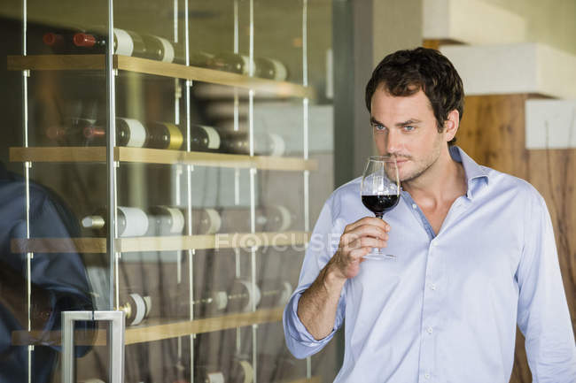 Man smelling red wine in wineglass — Stock Photo