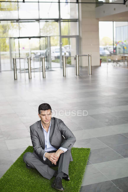 Businessman relaxing on grass mat in office lobby — Stock Photo