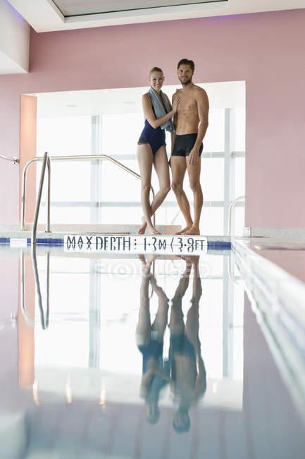 Sorridente coppia sottile in piedi a bordo piscina — Foto stock