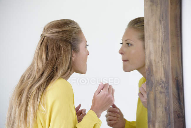 Elegant woman examining make-up in mirror — Stock Photo