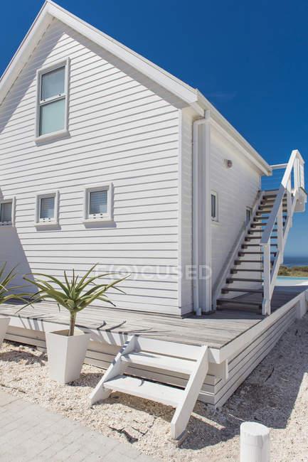 Facciata della casa di legno moderna bianca sotto il chiaro cielo — Foto stock