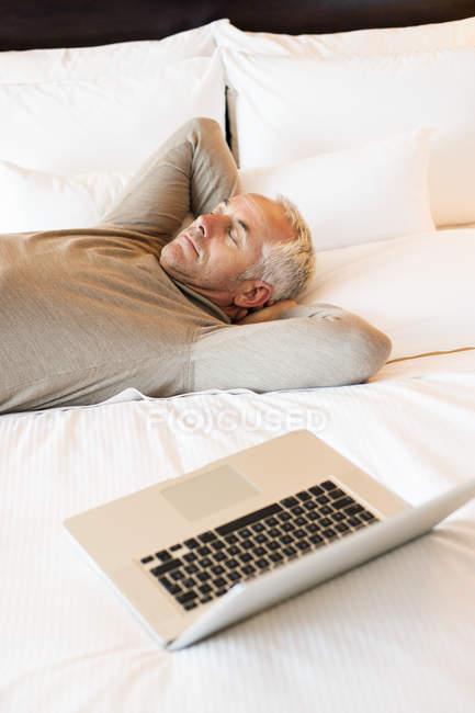 Homme se reposant sur le lit avec ordinateur portable dans la chambre d'hôtel — Photo de stock