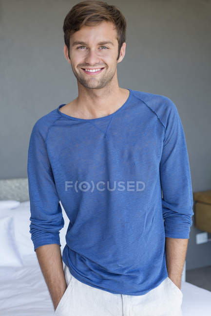 Portrait of man smiling with hands in pockets in bedroom — Stock Photo