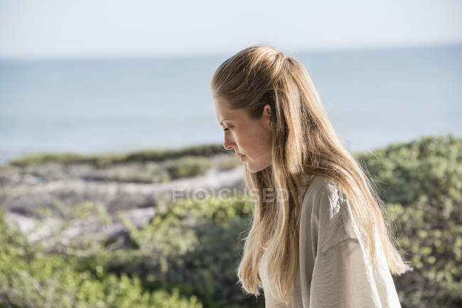 Close-up of thoughtful mid adult woman on beach — Stock Photo