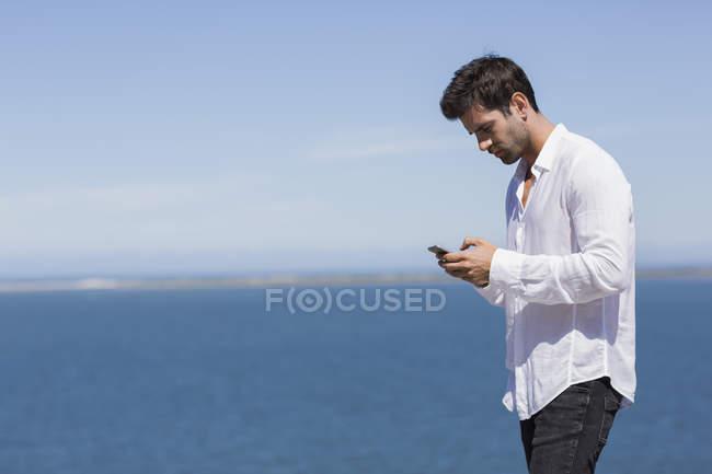 Pensive man in white shirt using smartphone at lake shore — Stock Photo