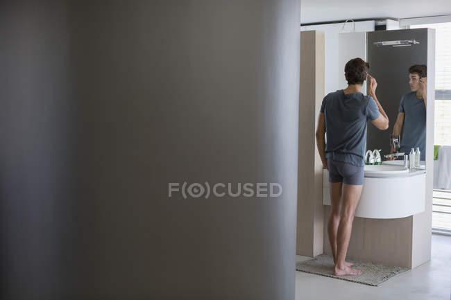 Giovane uomo che controlla i capelli nello specchio in bagno — Foto stock