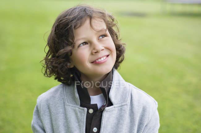 Крупный план мальчика, улыбающегося на зеленом поле — стоковое фото
