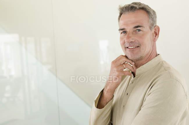 Retrato de hombre maduro sonriente de pie frente a la pared - foto de stock