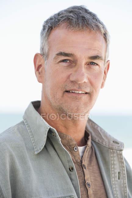 Retrato de hombre maduro confiado reflexivo mirando a la cámara al aire libre - foto de stock
