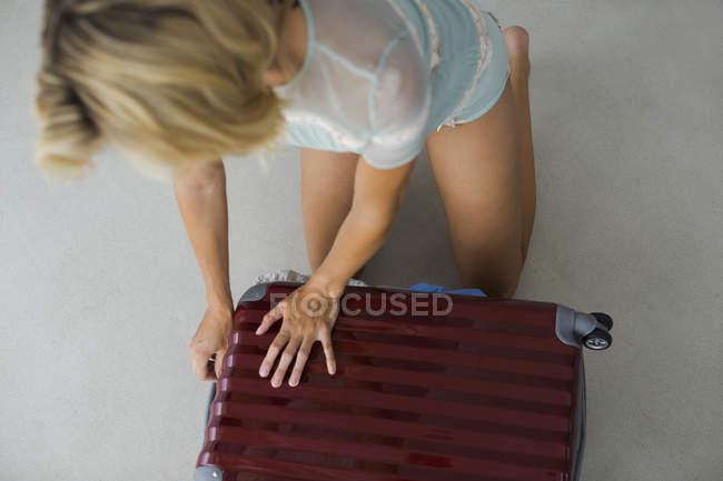Закри блондин молодої жінки намагаються закрити переповнення чемодан — стокове фото