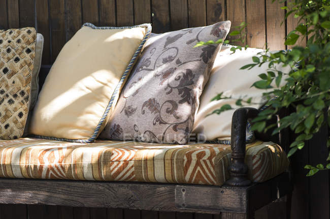 Close-up of couch with colorful pillows in sunlight — Stock Photo