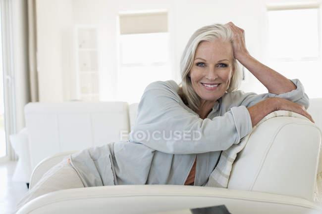 Портрет улыбающейся пожилой женщины, сидящей на диване — стоковое фото