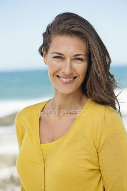 Porträt einer Frau mit braunen Haaren, die am Strand lächelt — Stockfoto