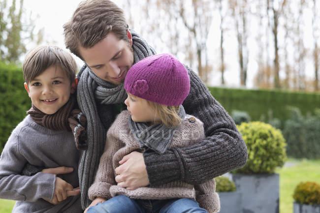 Чоловік обіймаючи усміхнені діти на відкритому повітрі — стокове фото