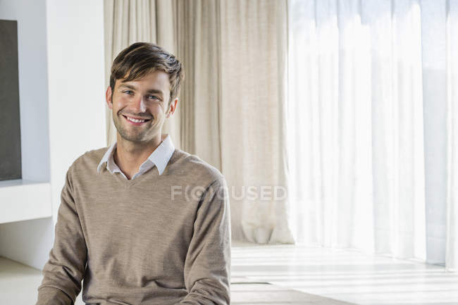 Portrait of smiling man sitting in living room — Stock Photo