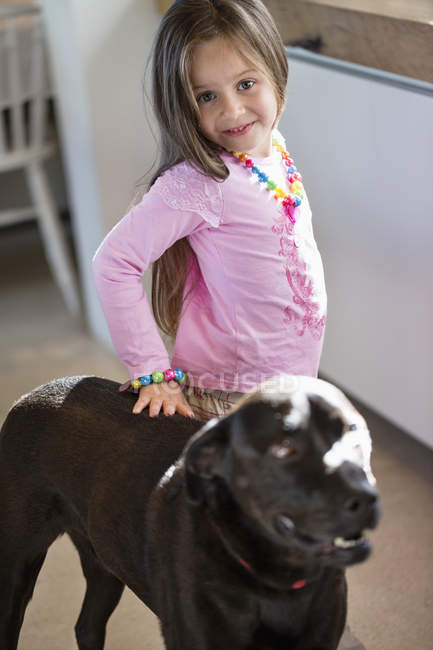 Portrait of smiling little girl standing with dog at home — Stock Photo