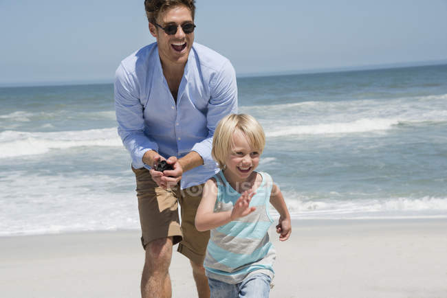 Young man playing with son on summer beach — Stock Photo