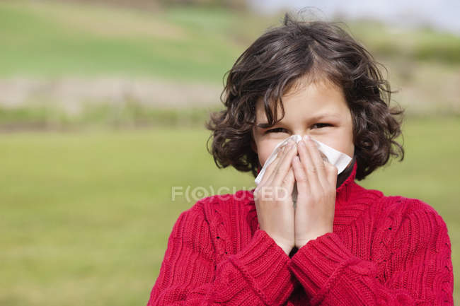 Portrait of boy blowing nose in field — Stock Photo