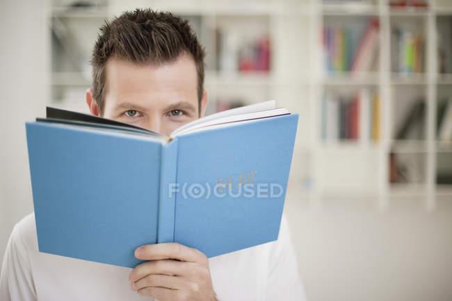 Портрет игривого человека с книгой перед лицом — стоковое фото